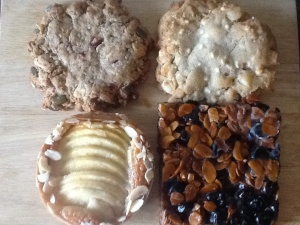 Clockwise from top left: granola cookie, macadamia white chocolate cookie, cherry almond square, apple almond tart